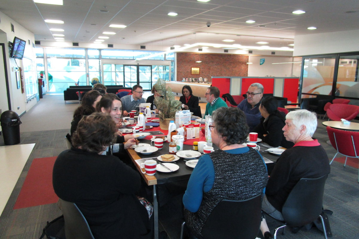 13 staff enjoying breakfast and te reo Māori around the dining table